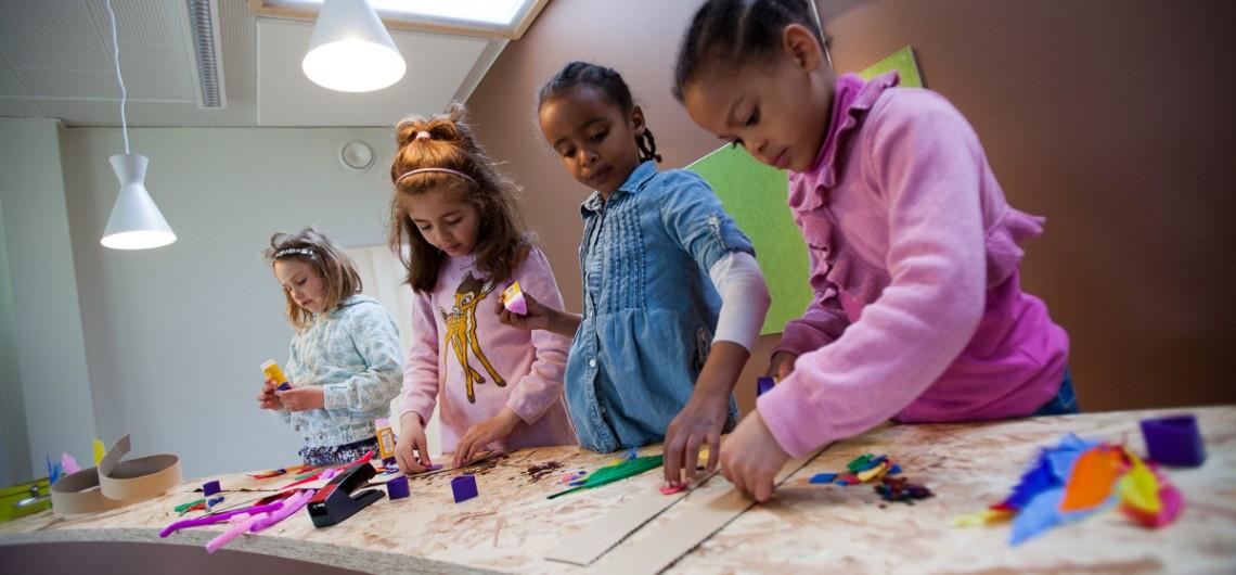 børn arbejder ved arbejdsdesk i børnehave
