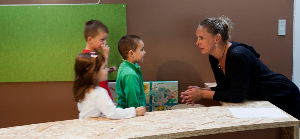 Der snakkes børn og voksne imellem over arbejdsdesk i værksted i børnehave. børn og voksne i øjenhøjde