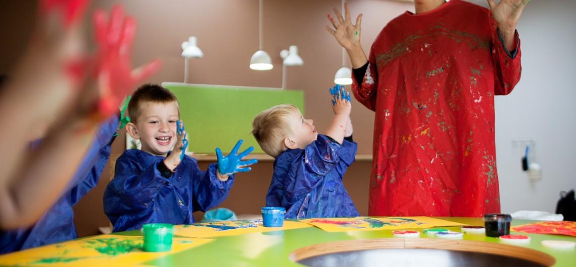 børn viser fingre med maling på. Fingermaling