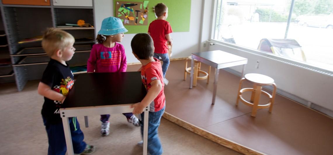 børn flytter fleksibelt arbejdsbord i alu. podie til leg. rum i rummet