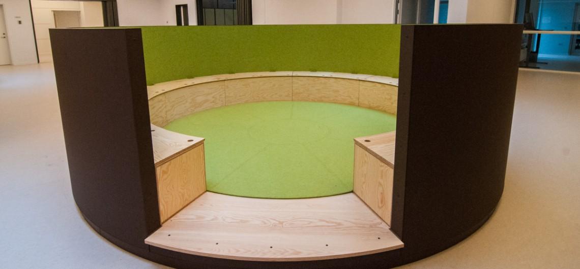 """møderum til børn. langs væggene indrammes """"tinget"""" med bænke og kasser til konstruktionsleg"""
