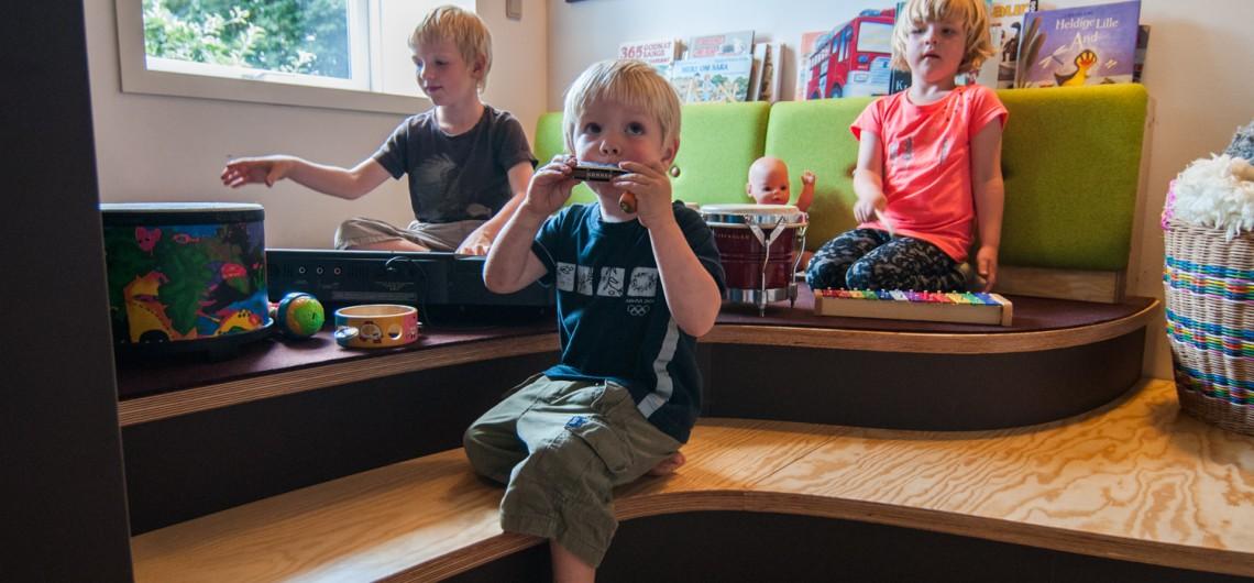 legepodie med børn. Rygstøtter polstret med filt. plads til udstilling af bøger