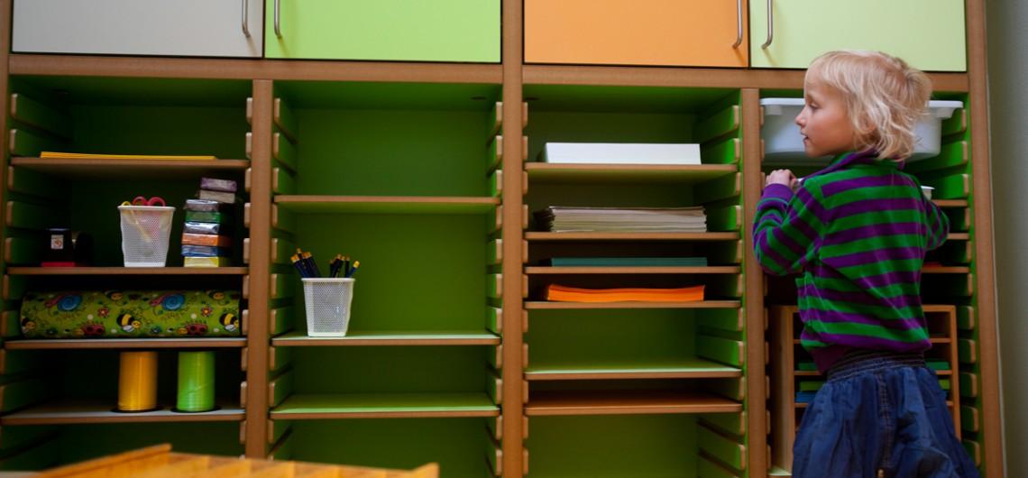 Reol i Børnehuset Bjørnemosen. indrettet med tegnematerialer i børnehøjde. gør børn selvhjulpne